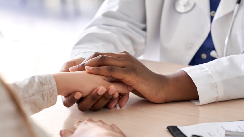 doctor holding the hand of their patient with care