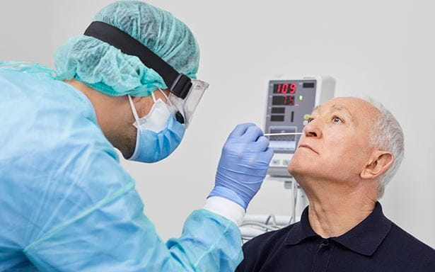 man getting nasal swab for COVID-19 test